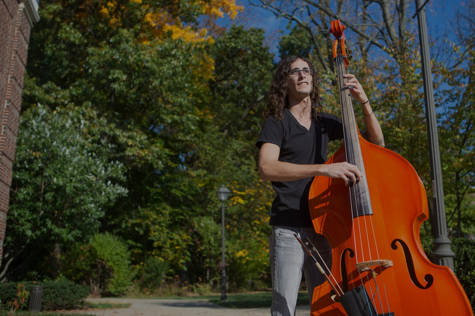 TCNJ student playing a double bass outside of Music Building